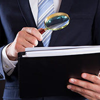 Human Resources executive looking at documents with magnifying glass