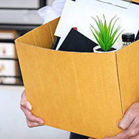 Male employee who resigned position at company holding box of personal effects